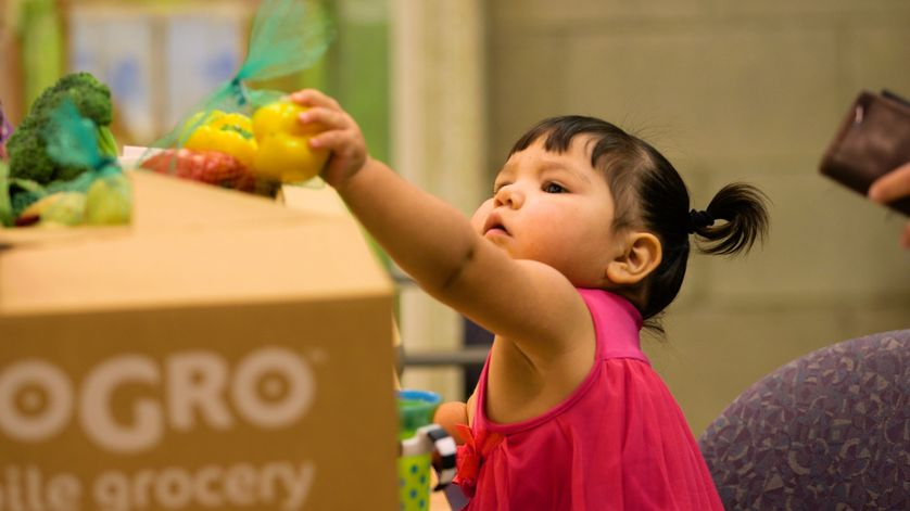 Little girl reaching for MoGro fresh produce.