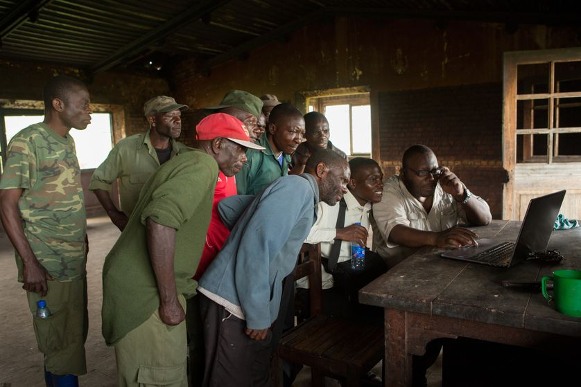 Group of men review camera trap images.