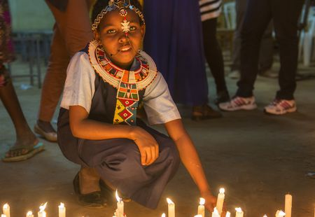 A young African girl during a candle-lighting ceremony