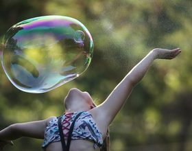 Child plays with large bubble at Camp Erin