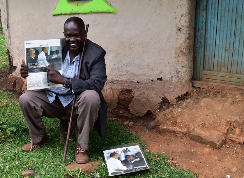 Linet's father shows off a newspaper article about her meeting with President Obama during his visit to Kenya.