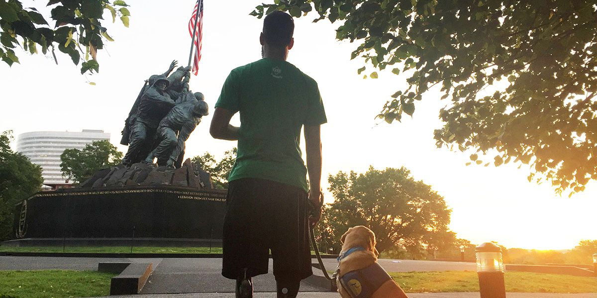 Army sergeant and his guide dog with flag