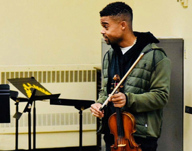 Young violinist teaches kids in school