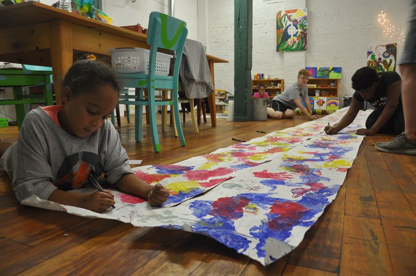 adult and children work on long footprint scroll