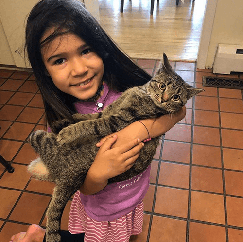 Child holds special needs cat