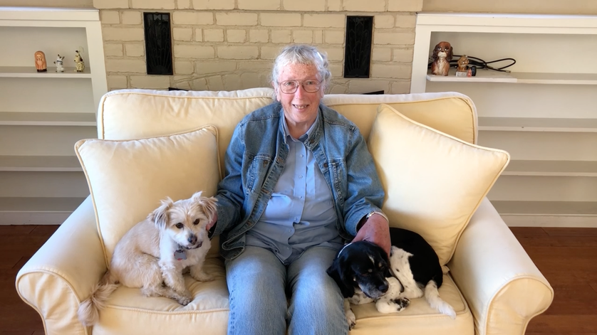 older woman with two dogs on couch