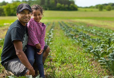 Father and daughter pose in front of farm