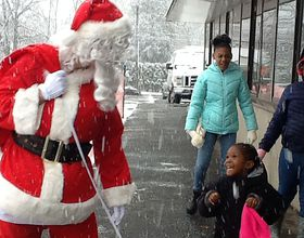 Santa surprises kid at gift giving event