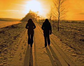 Two people walk in snow