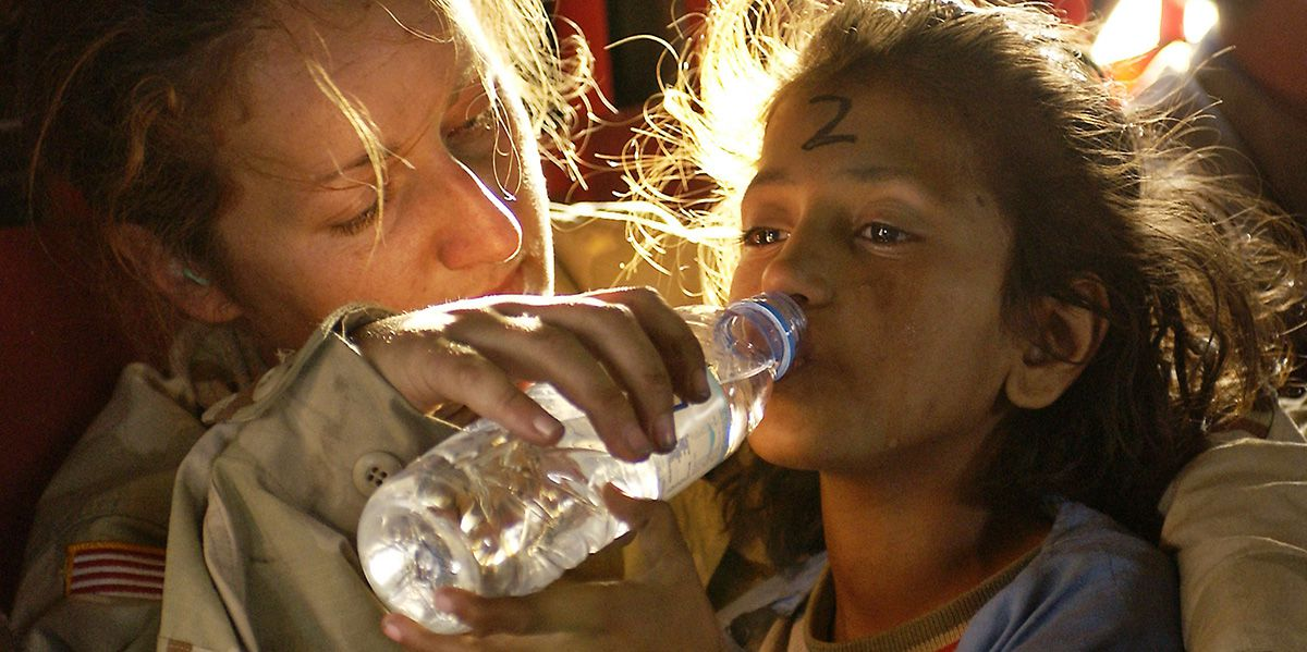 Aid gives water to little girl