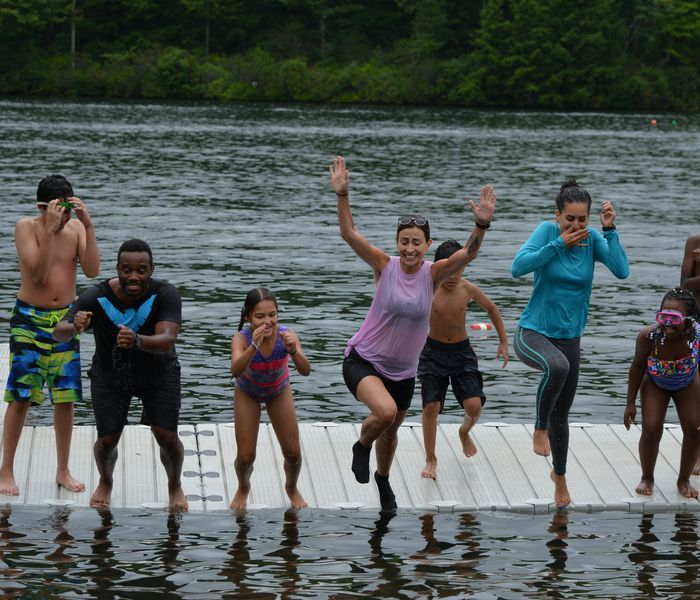 group of people jump in lake
