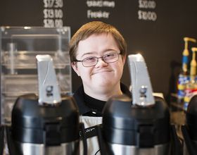 an employee smiles behind coffee containers