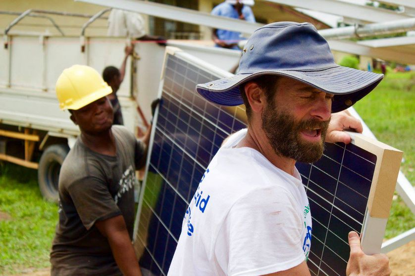 two men carry solar panel