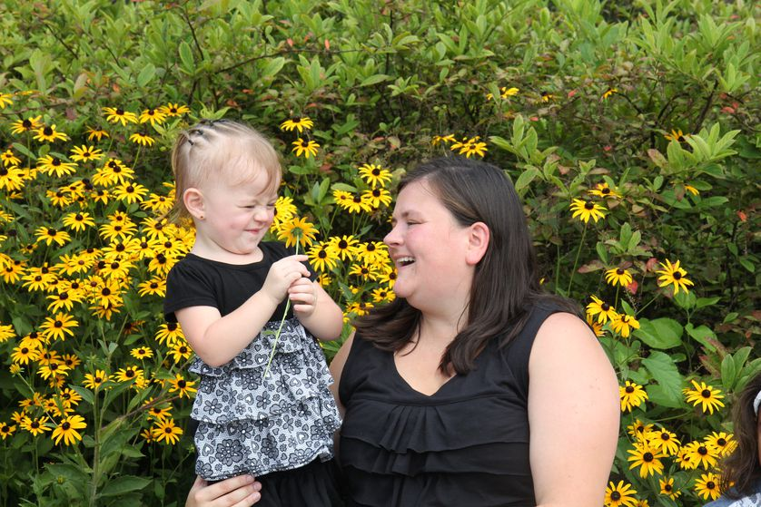 mother and child with flowers laugh
