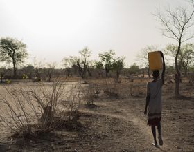 woman walks alone in south sudan