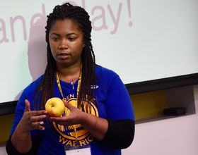 a teacher teaches nutrition with apple