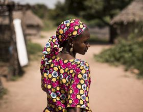 woman walks through village of Mali
