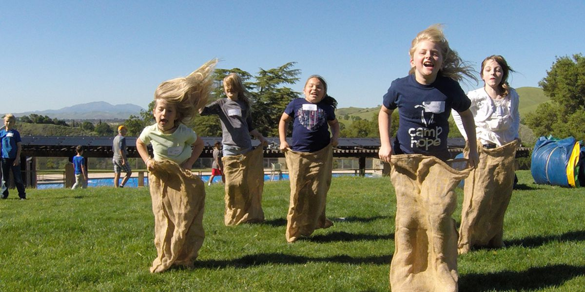 campers race in potato sacks outside