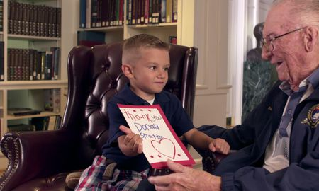 WWII vet and child share a card