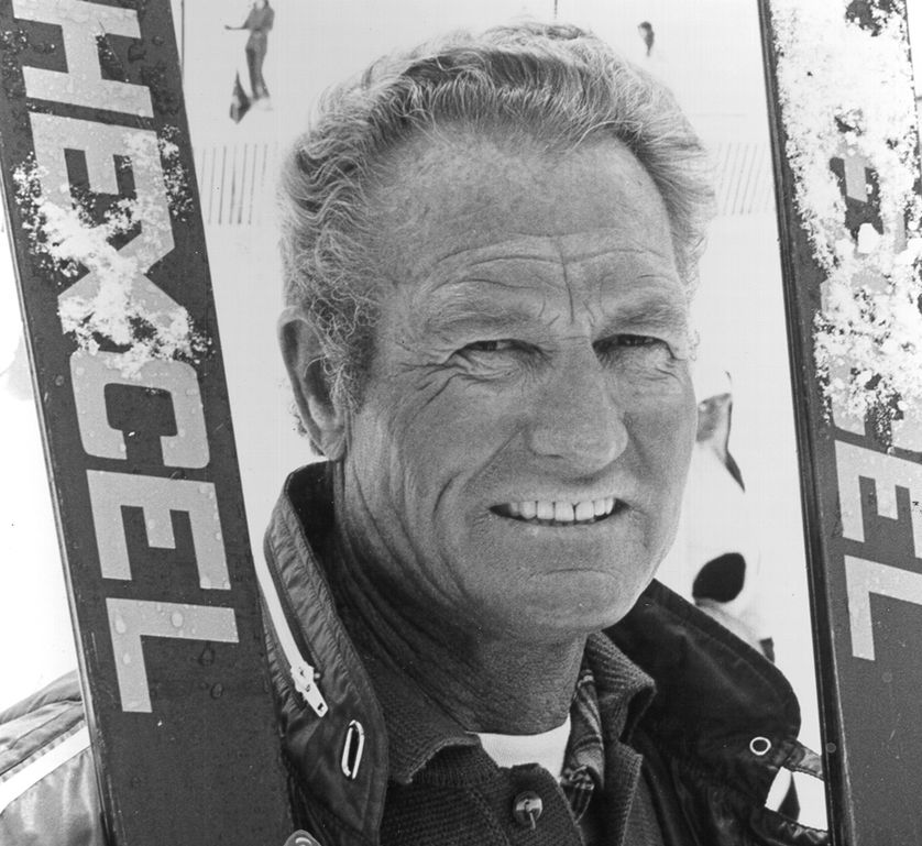 man poses with skis in b&w