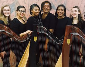 group of women and girls pose with harp instruments
