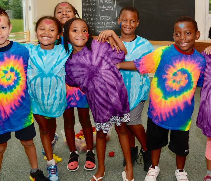 Young kids pose in tie-dye t-shirts