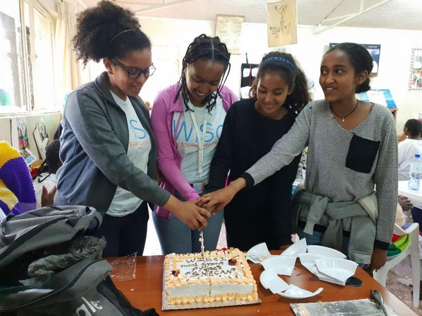 group of women celebrate over cake