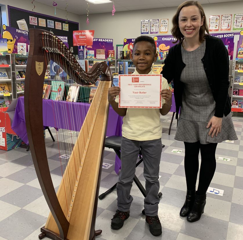 a child poses in a classroom with harp and teacher