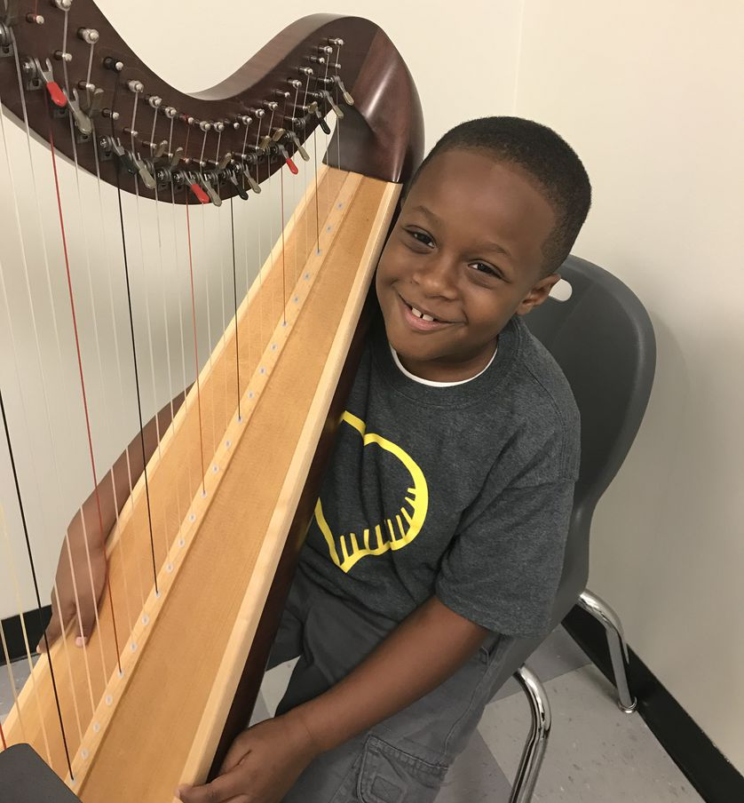 young boy holds harp