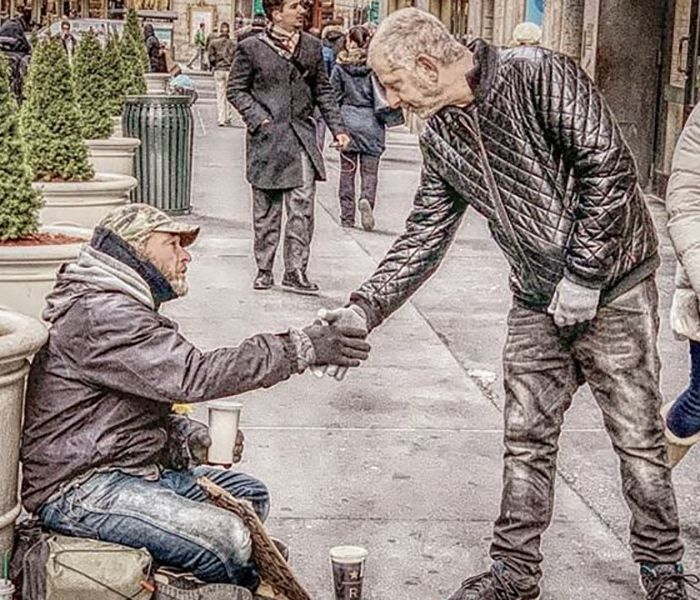 Founder shakes hands with homeless man on street