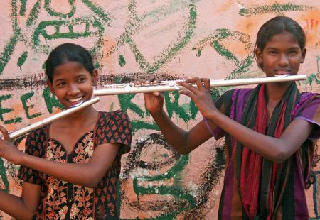 Two girls play flute in India