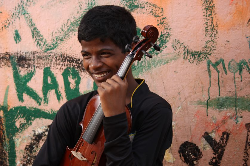 Young Indian boy plays violin outside