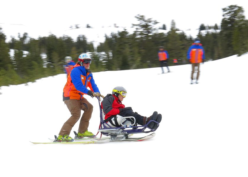 ski instructor helps disabled person on the slopes