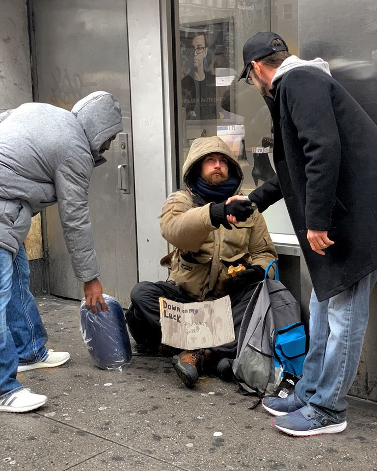 Man shakes homeless person's hand on street