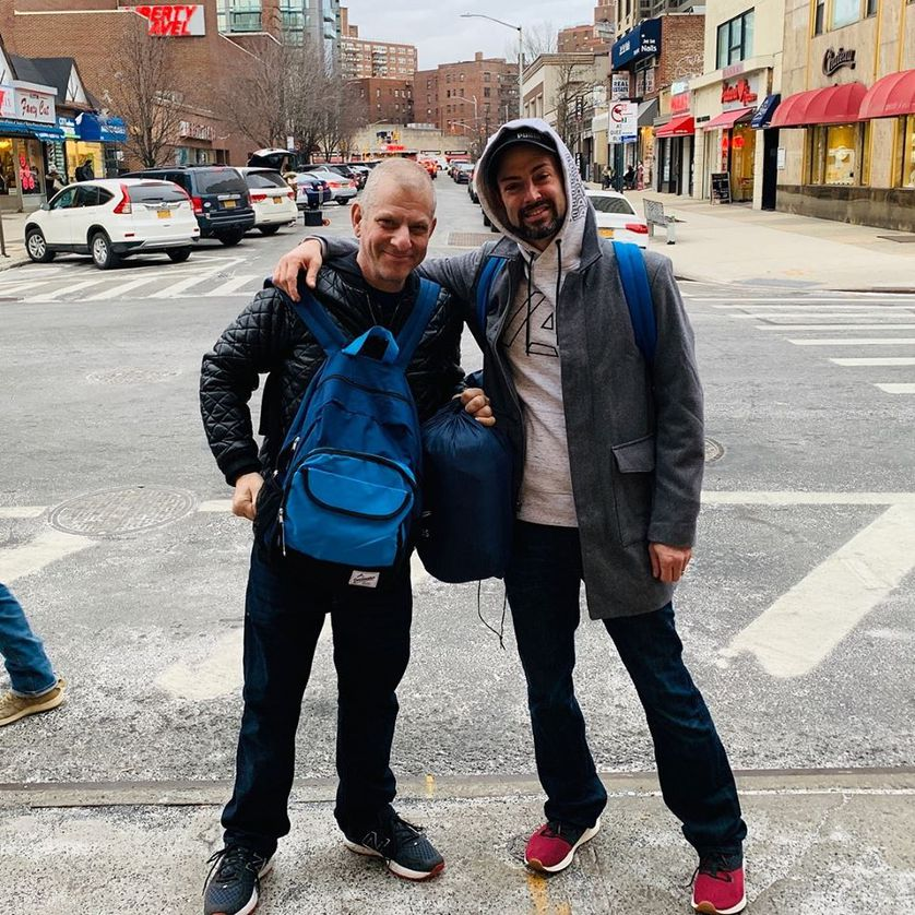 the two founders hold backpacks on street