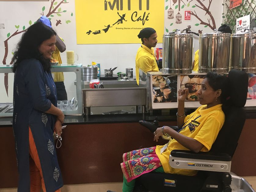 a customer at the cafe greets employee in wheelchair