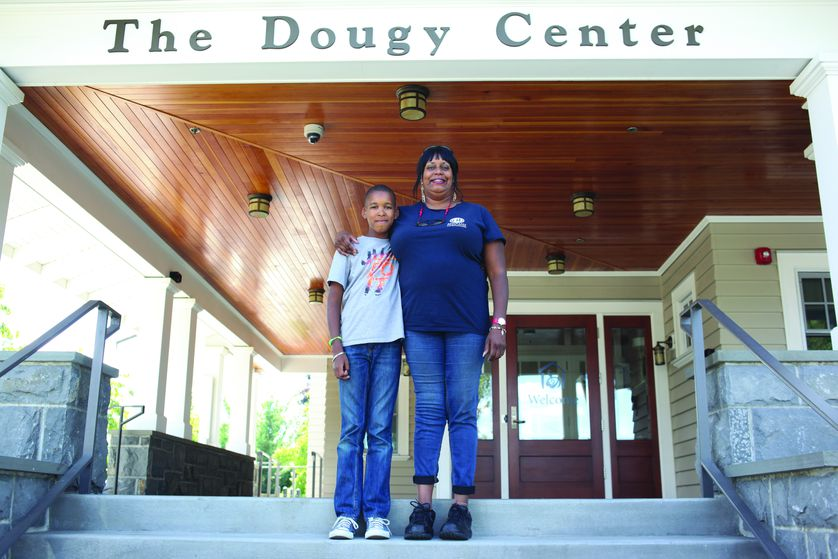 older woman and small child stand on steps of dougy center