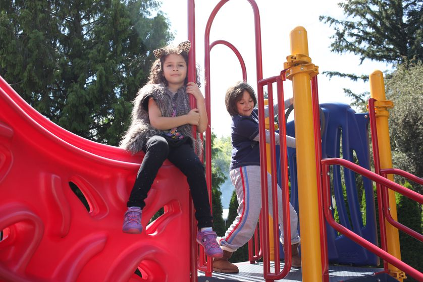 children play outside on playscape