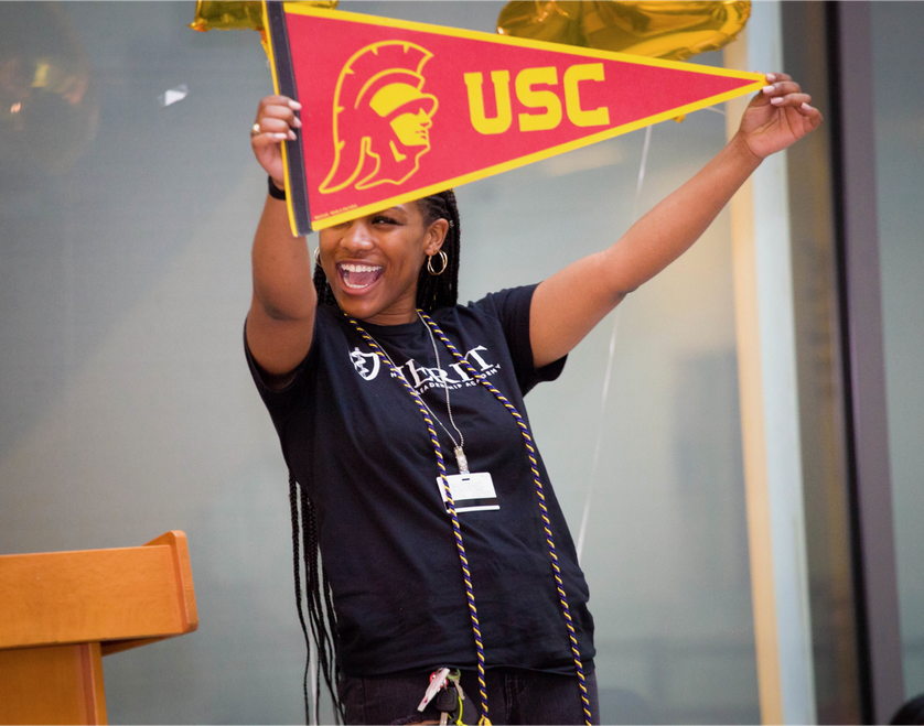 high school student celebrates with USC pendant