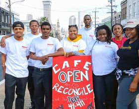 Group of Cafe Reconcile participants with New Orleans in the background