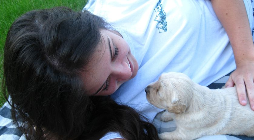 young girl cuddles puppy