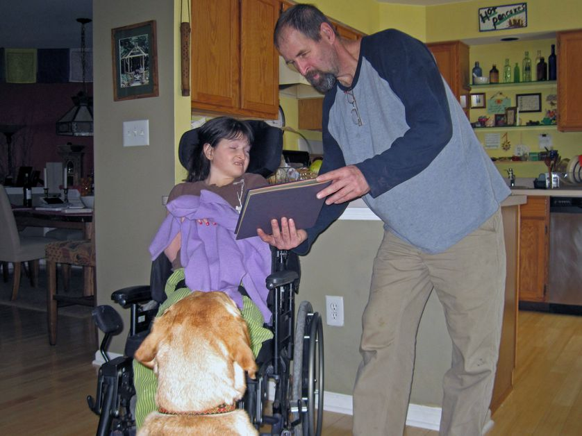service dog watches child while dad reads a story