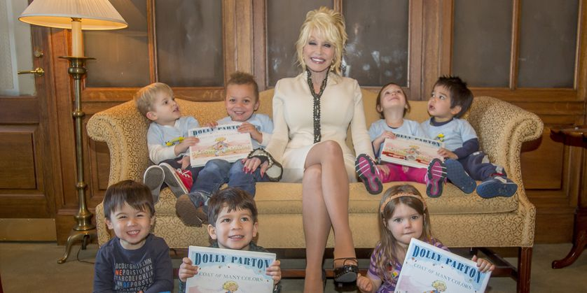 dolly parton sits on couch reading books to kids