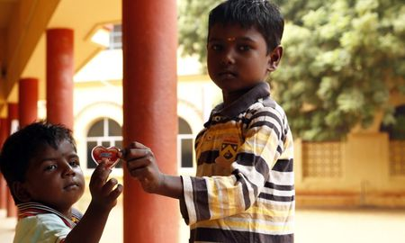 two children pose with heart in india