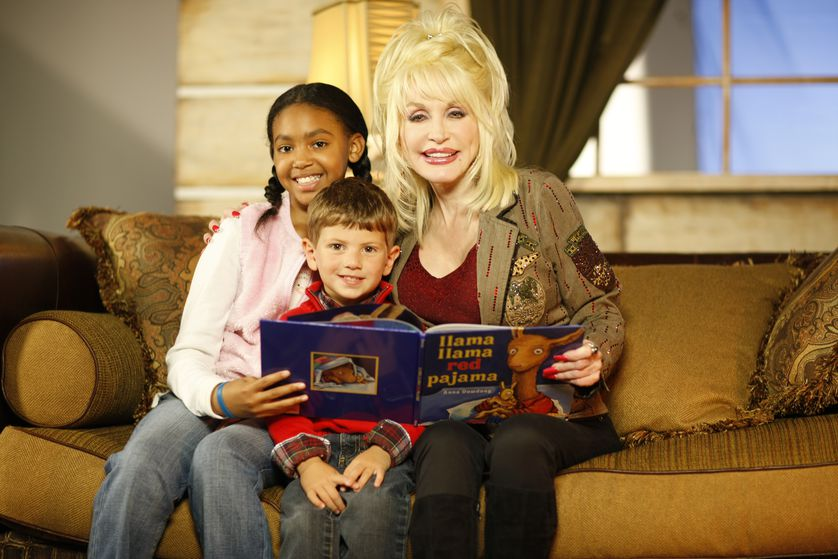 Dolly sits on couch with books and kids