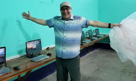 man shows off completed computer lab in peru